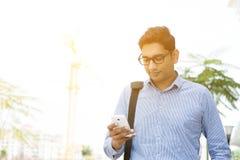 发短信使用智能手机的印地安商人 库存照片