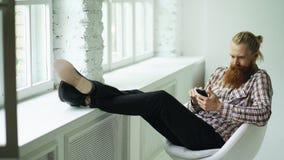 发短信使用智能手机的有胡子的年轻行家人sms,当在与他的腿的offce椅子坐窗台时 免版税图库摄影