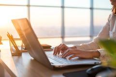 发短信使用膝上型计算机和互联网的女性远程工作人员,在网上运作 键入在家办公室,工作场所的自由职业者 免版税库存照片
