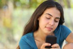 发短信在一个巧妙的电话的俏丽的少年女孩 免版税库存照片