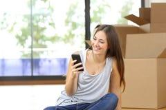 发短信在一个巧妙的电话的妇女移动的家 图库摄影