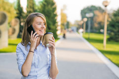 发短信在一个巧妙的电话的美丽的妇女在有绿色的一个公园 免版税库存图片