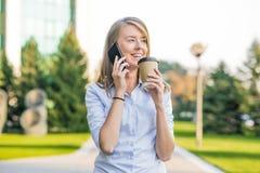 发短信在一个巧妙的电话的美丽的妇女在有绿色的一个公园 库存图片