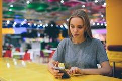 发短信在一个餐馆大阳台的巧妙的电话的女孩有未聚焦的背景 免版税库存照片