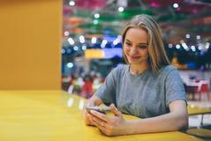 发短信在一个餐馆大阳台的巧妙的电话的女孩有未聚焦的背景 图库摄影
