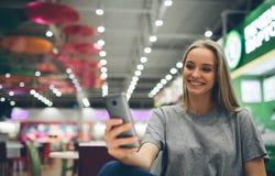 发短信在一个餐馆大阳台的巧妙的电话的女孩有未聚焦的背景 免版税库存图片