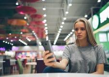 发短信在一个餐馆大阳台的巧妙的电话的女孩有未聚焦的背景 库存图片