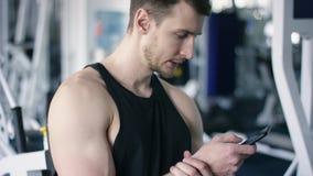 发短信在健身房的智能手机的年轻爱好健美者接近的射击,当休息在锻炼期间时 股票录像