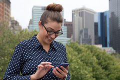 发短信在城市的年轻职业妇女 免版税图库摄影