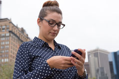 发短信在城市的年轻职业妇女 图库摄影