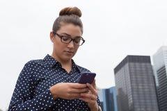 发短信在城市的年轻职业妇女 免版税库存照片