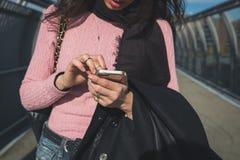 发短信在城市街道的妇女的细节 库存图片