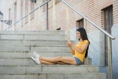 发短信在她巧妙的电话的可爱的拉丁妇女 免版税库存图片