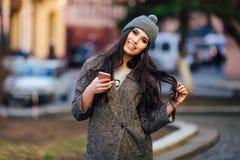 发短信在她的在春天城市街道上的手机的年轻美丽的偶然女孩 免版税库存照片
