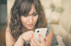 发短信在她的手机的少妇 免版税库存照片