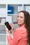 发短信在她的智能手机的微笑的女实业家 免版税库存图片