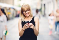 发短信在她的智能手机的愉快的妇女 库存图片