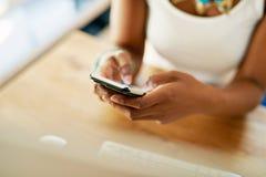 发短信在她的机动性的年轻非洲妇女 库存图片
