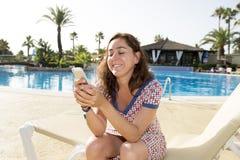 发短信在她的电话的可爱的妇女在度假 免版税图库摄影
