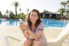 发短信在她的电话的可爱的妇女在度假 库存图片