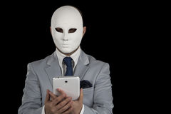 发短信在巧妙的电话的人佩带的面具, 库存图片
