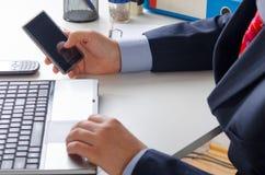 发短信在巧妙的电话的商人在办公室 免版税图库摄影