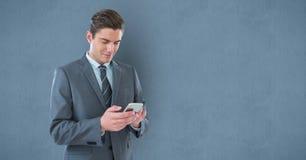 发短信在巧妙的电话的商人对墙壁 库存照片