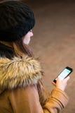 发短信在巧妙的电话的妇女在晚上 免版税图库摄影
