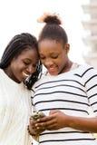 发短信在巧妙的电话的非洲青少年的女孩 免版税图库摄影