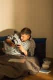 发短信在床上的人 免版税库存照片