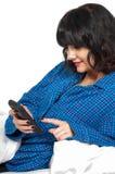 发短信在床上的妇女 免版税库存图片