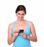 发短信在手机的拉丁运动的妇女 库存照片