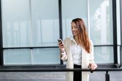 发短信在手机的美丽和可爱的女实业家 免版税库存图片