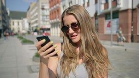 发短信在手机的年轻愉快的妇女在晴天期间在城市 股票视频