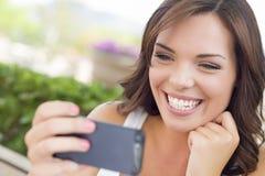 发短信在手机的年轻成年女性户外 免版税库存图片