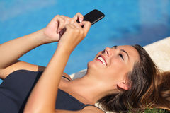 发短信在旅馆游泳池边的一个巧妙的电话的女孩在度假 图库摄影