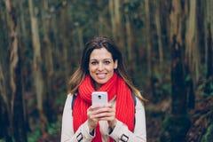 发短信在智能手机的妇女在旅行期间对森林 免版税库存图片