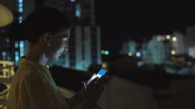 发短信在智能手机的年轻微笑的妇女特写镜头站立在屋顶大阳台在晚上 免版税库存图片