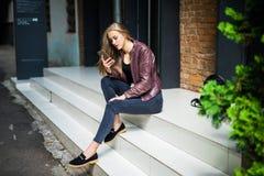 发短信在智能手机的年轻美丽的微笑的适合的妇女,当基于台阶时 库存照片