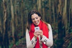 发短信在智能手机的愉快的妇女在旅行期间对森林 图库摄影