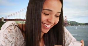 发短信在智能手机的拉提纳女孩在公园 免版税库存照片