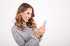 发短信在智能手机的美丽的妇女 库存照片