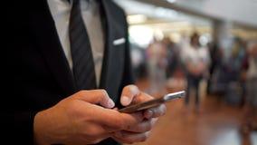 发短信在智能手机,小配件,现代技术的西装的人 免版税库存图片
