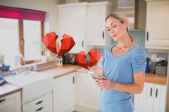 发短信在有数字式引起的红色心脏的手机的妇女 库存图片