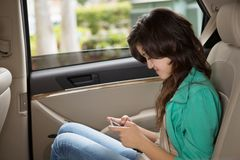 发短信在汽车的十几岁的女孩 免版税库存图片