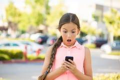 发短信在流动,巧妙的电话的震惊孩子 免版税库存照片