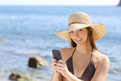 发短信在海滩的一个巧妙的电话的美丽的愉快的妇女 免版税库存照片