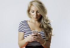 发短信在电话的白肤金发的拉提纳女孩 免版税图库摄影