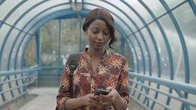 发短信在电话的逗人喜爱的非裔美国人的女孩在片剂,非洲的女性,美丽的黑人妇女屏幕上出席了与 股票视频