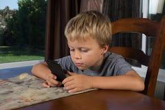 发短信在电话的年轻男孩 免版税库存照片